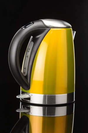 Yellow painted stainless steel electrical kettle on black mirror background Zdjęcie Seryjne