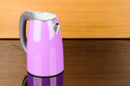 Purple stainless steel isolated cordless electrical kettle with black plastic handle on the wood mirror background with copy space