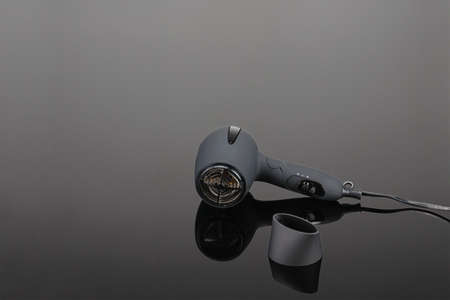 Grey mat electrical hand-held hair dryer for hair salon or barber shop on the grey mirror background