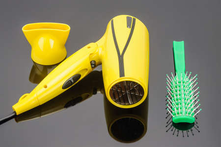 Yellow foldable electrical hand-held hair dryer for hair salon or barber shop on the grey mirror background with green comb