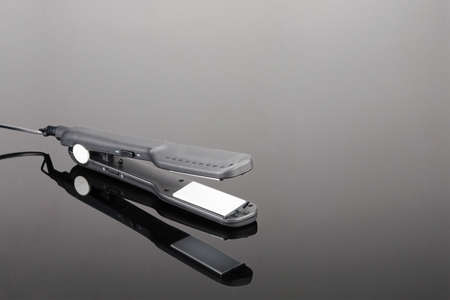 Grey mat electrical hand-held hair iron for hair salon or barber shop on the grey mirror background