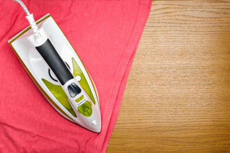 Electrical hand iron on the wood background with T-shirt and copy space