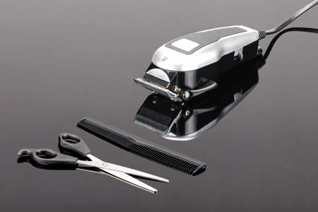 Electric hand-held hair clipper with accessory  for hair salon or barber shop on the grey mirror background with copy space Фото со стока