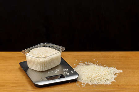 A stainless steel electronic scale with rice on woody background.