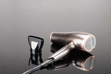 Brown electrical hand-held hair dryer for hair salon or barber shop on the grey mirror background Фото со стока