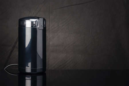 Black coffee grinder with transparent plastic lid on the black mirror background. Copy space