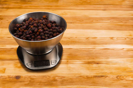 Dry hips in a stainless steel bowl on a stainless steel electronic scale on a natural wood background. Copy space.