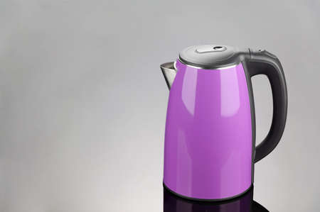 Stainless steel cordless electrical kettle with black plastic handle on grey mirror background. Copy space.