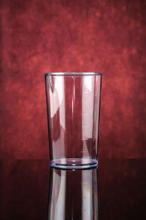 Transparent measure glass for black plastic electrical hand blender on the red mirror background.