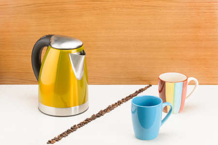 Electrical kettle with mugs and handful coffee beans on the wood and marble background Foto de archivo