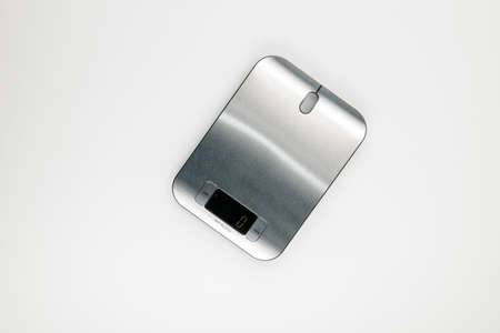 A stainless steel electronic scale on white background. Foto de archivo