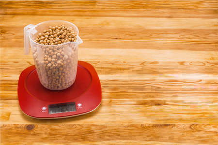 Chickpea in a transparent measure cup  on an red plastic electronic scale on a natural wood background. Copy space. Foto de archivo