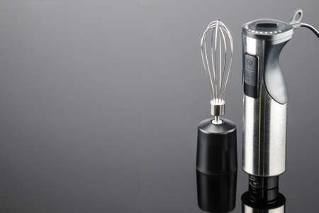 Black plastic electrical hand blender with stainless steel body and accessory on the grey mirror background. Copy space