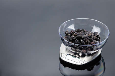 Dry plum in a transparent bowl on a stainless steel electronic scale on grey mirror background. Copy space.