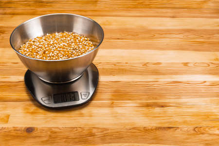 Corn in a stainless steel bowl on a stainless steel electronic scale on a natural wood background. Copy space.