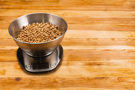 Chickpea in a stainless steel bowl on a stainless steel electronic scale on a natural wood background. Copy space. Foto de archivo