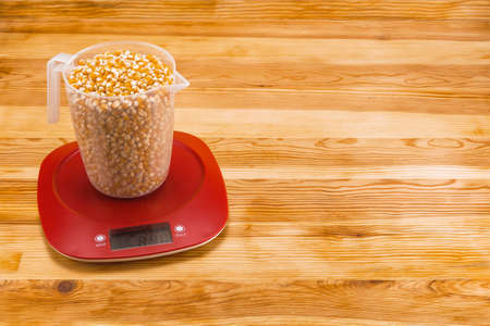 Corn in a transparent measure cup  on an red plastic electronic scale on a natural wood background. Copy space. Foto de archivo