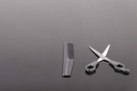 Comb and  hair clipper with accessory  for hair salon or barber shop on the grey mirror background with copy space Foto de archivo