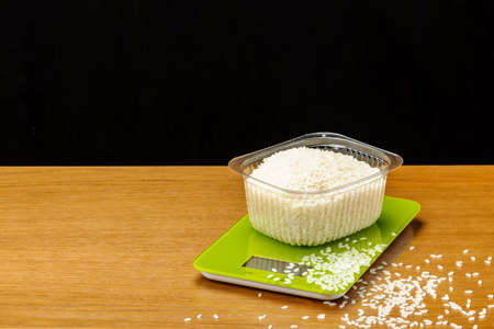 A glass electronic scale with rice on woody background. Foto de archivo