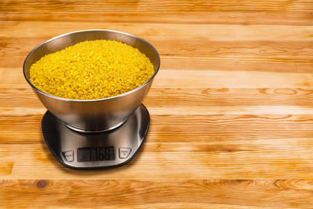Bulgur in a stainless steel bowl on a stainless steel electronic scale on a natural wood background. Copy space. Foto de archivo