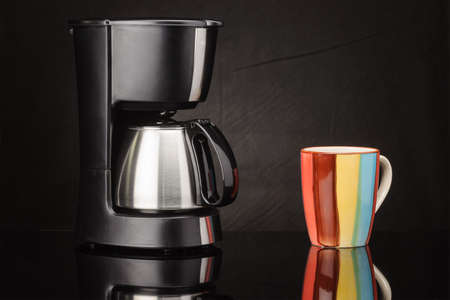 Electrical coffee machine with stainless steel coffee pot and mug on the black mirror background Foto de archivo