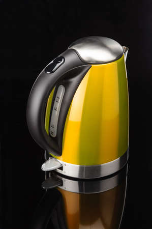 Yellow painted stainless steel electrical kettle on black mirror background Foto de archivo