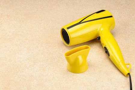 Yellow foldable electrical hand-held hair dryer for hair salon or barber shop on the marble background with copy space