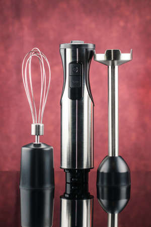 Black plastic electrical hand blender with stainless steel body and accessory on the red mirror background.