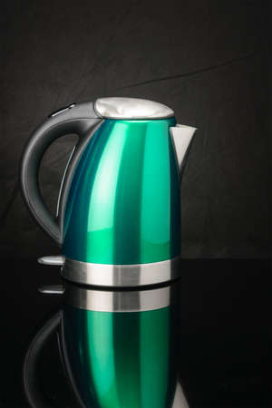 Green painted stainless steel electrical kettle on black mirror background