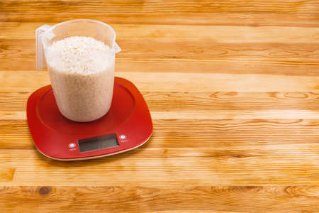 Rice in a transparent measure cup  on an red plastic electronic scale on a natural wood background. Copy space. Foto de archivo