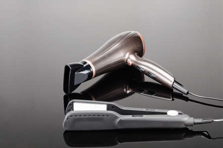 Grey mat electrical hand-held hair iron and brown dryer for hair salon or barber shop on the grey mirror background Foto de archivo