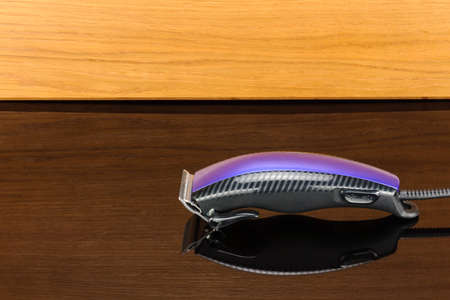 Electric hand-held hair clipper for hair salon or barber shop on the woody mirror background with copy space