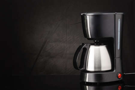Electrical coffee machine with stainless steel coffee pot on the black mirror background. Copy space.