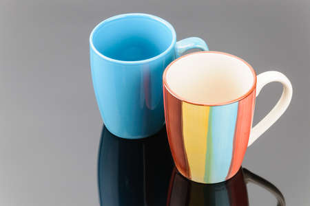 Couple of porcelain clay mug for coffee or tea on the grey mirror background
