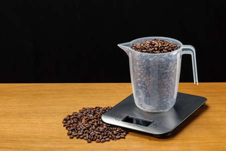 A stainless steel electronic scale with coffee beans on woody background. Foto de archivo
