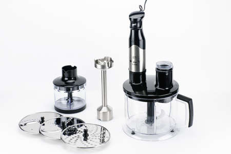 Black plastic electrical hand blender with accessories on the white matt background. Copy space