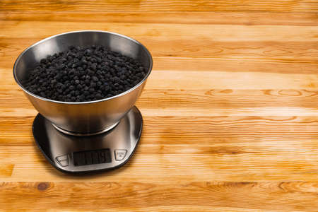 Dry blackberry in a stainless steel bowl on a stainless steel electronic scale on a natural wood background. Copy space.