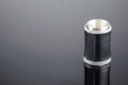 Black coffee grinder without lid on the grey mirror background. Copy space.