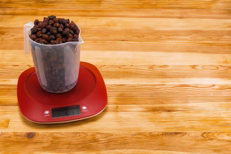 Dry hips in a transparent measure cup  on an red plastic electronic scale on a natural wood background. Copy space.