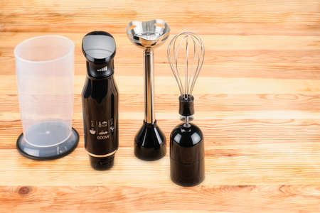 Black plastic electrical hand blender with accessories on the natural wood background. Copy space Foto de archivo