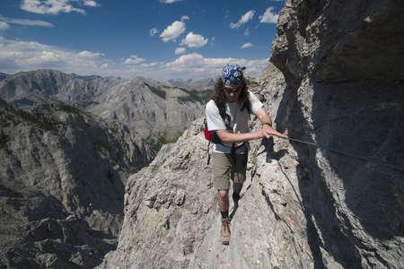 scrambling: alpinista oscuramento lungo la parete scoscesa, montagne rocciose