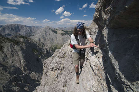 scrambling: mountaineer scrambling along steep wall, rocky mountains