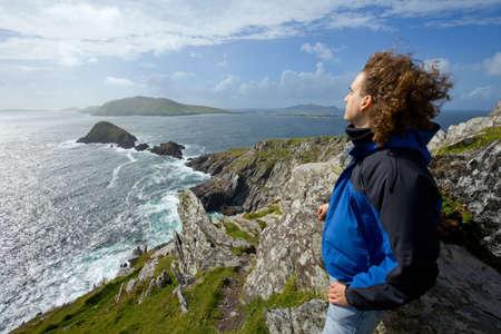 blasket islands: man on cliffs looking out towards blasket islands