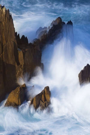 long exposure of ocean surf splashing against rock,