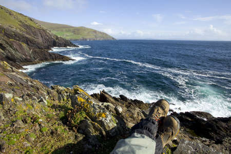 dunquin: man relaxing at irish coast, just legs and boots