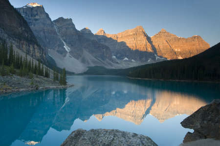 alpenglow: moraine lake with mountains and reflection in canadian yoho national park
