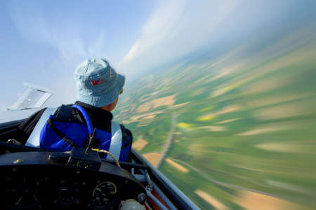 soaring in the sky with landscape rushing below, pilot and instruments in foreground Stock Photo