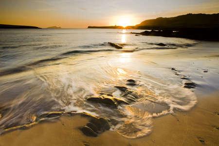 ebb: Fala walcowania na plaży na zmierzchu, Wysp i słońca w tle, długiego narażenia ze statywu Zdjęcie Seryjne