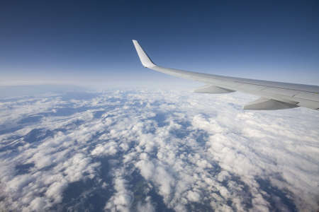 airfoil: airfoil with clouds and landscape below,aerial photo