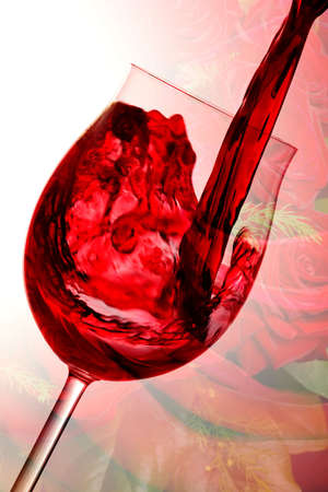 pouring red wine into wine glass, romantic roses in background